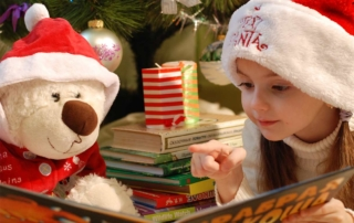 Child wearing a Santa hat reading a book
